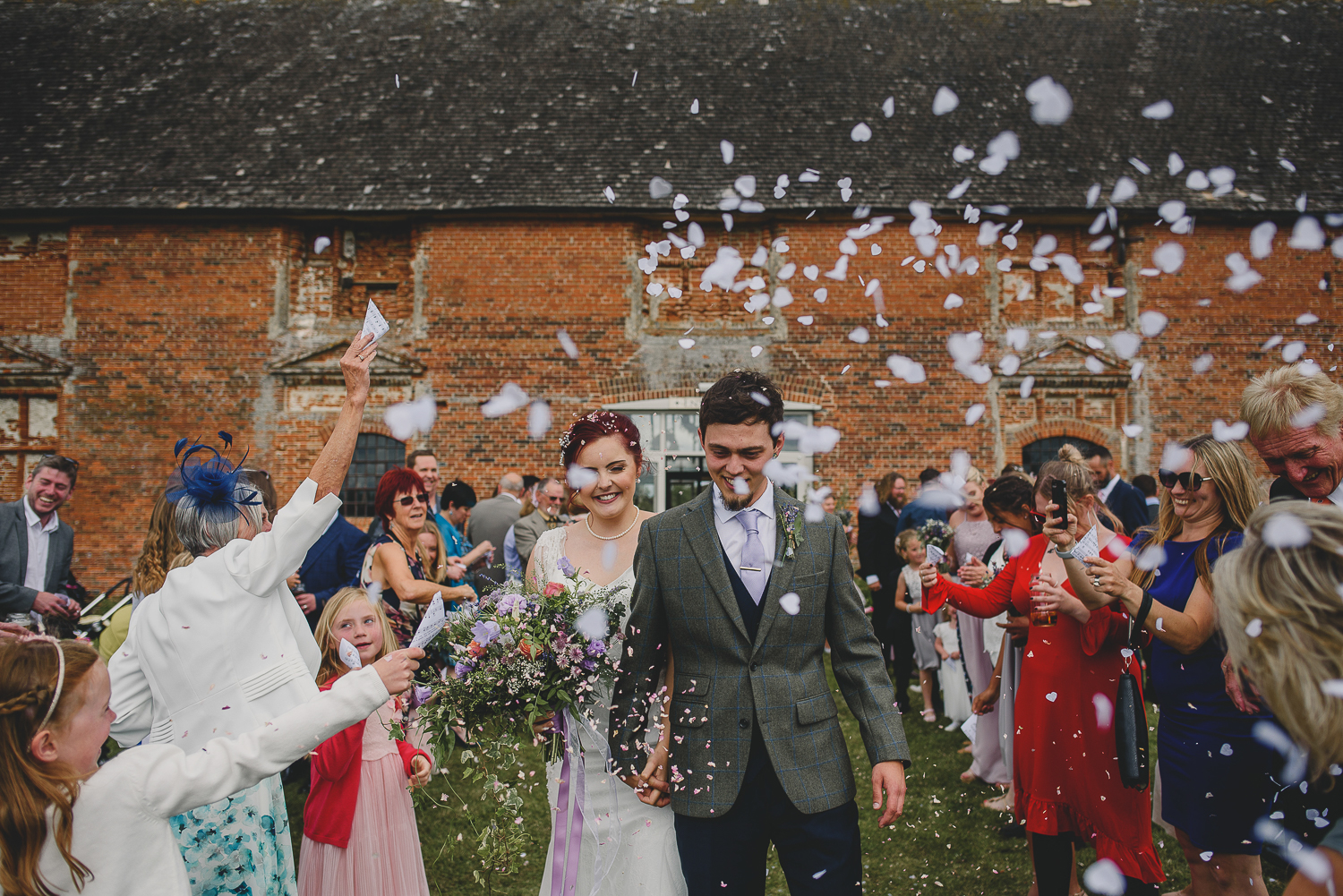 couple walk confetti line at godwick