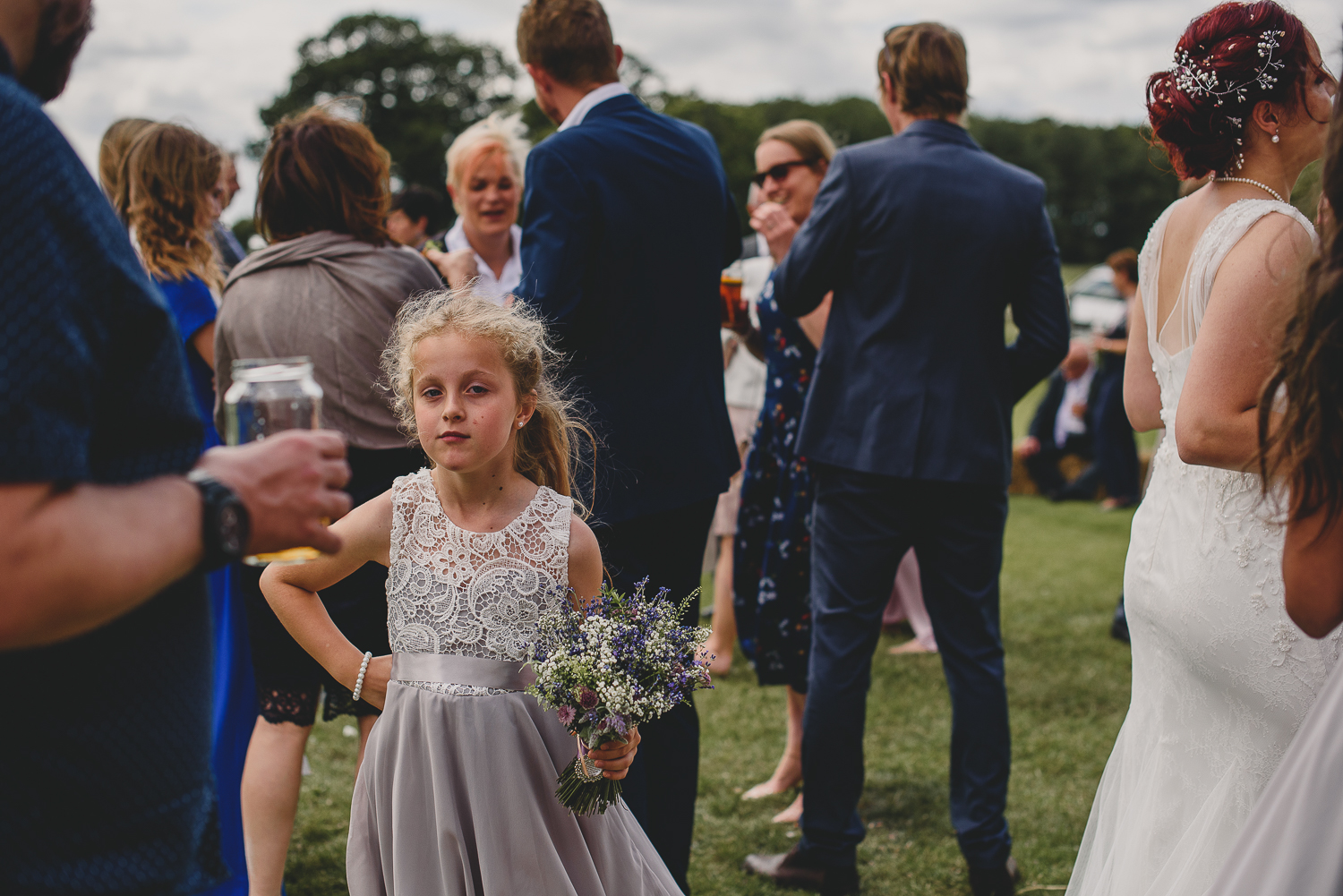 bridesmaid stands with hand on hip at wedding