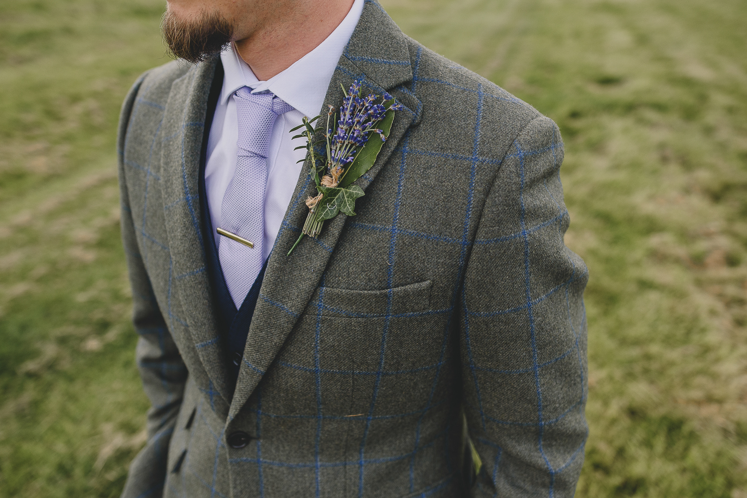 close up of button hole on groom's suit