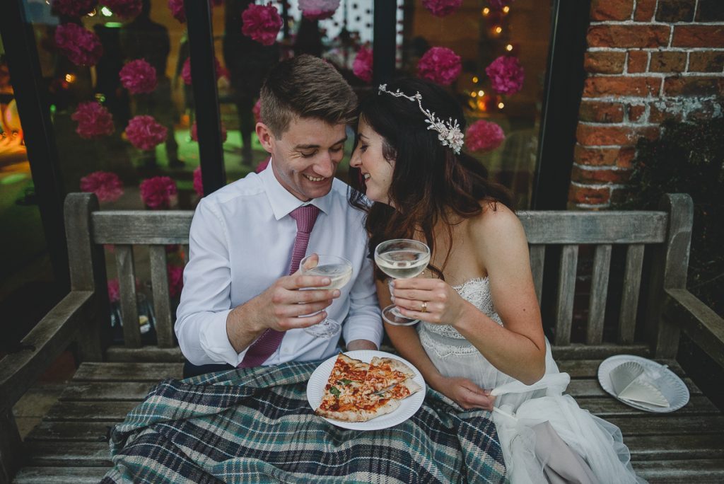 bride and groom eating pizza at wood farm barn