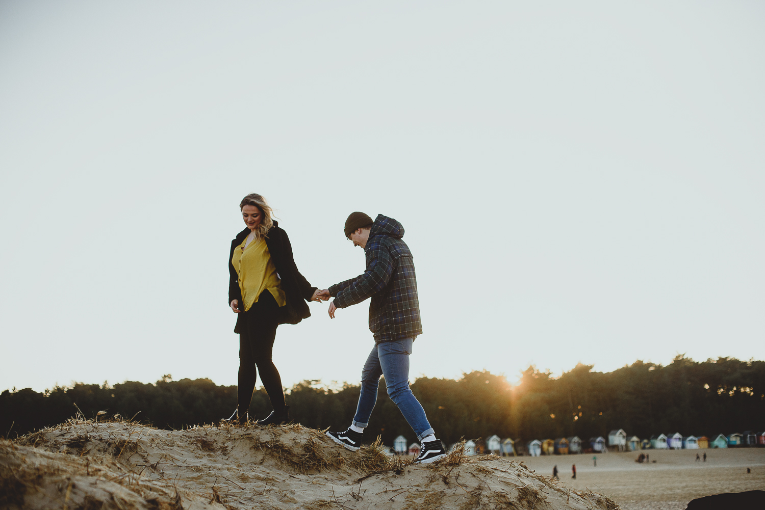 couple walking hand in hand on sand dunes