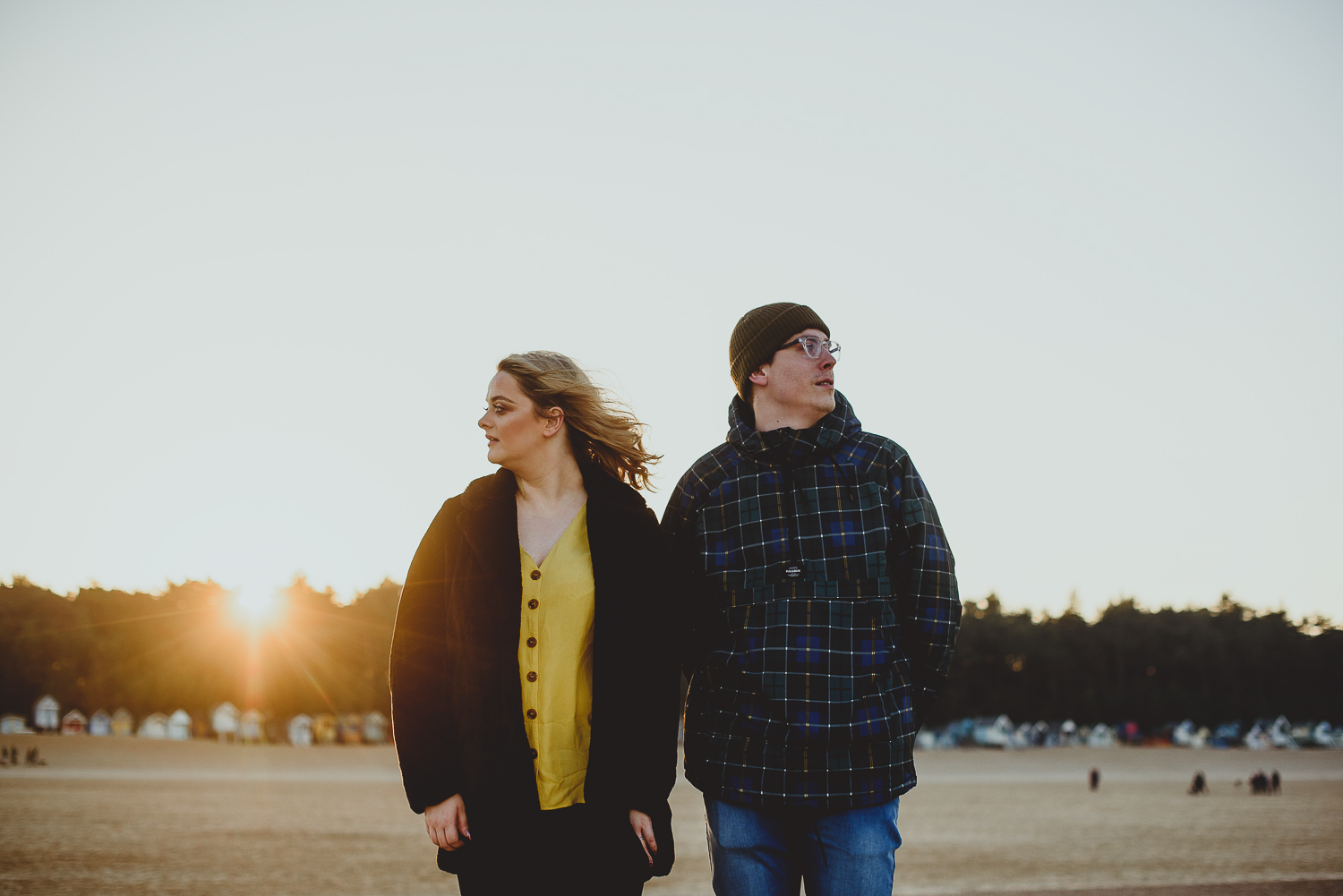 couple standing on wells beach at sunset