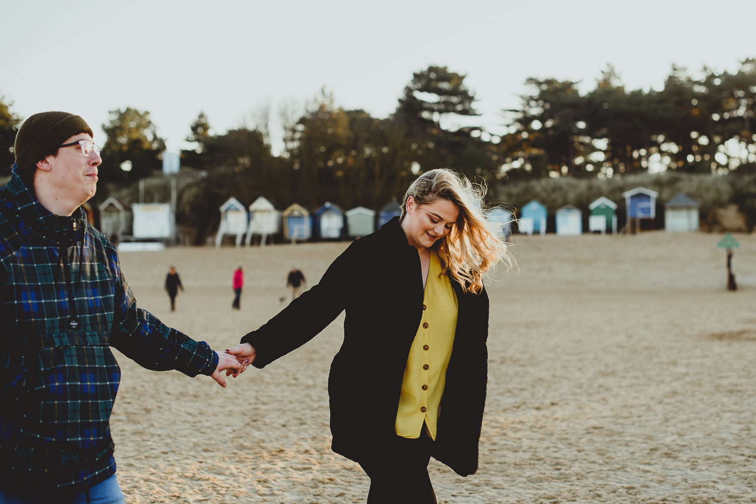 couple holding hands on the beach at wells norfolk