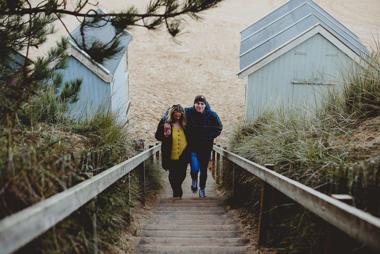 couple walking up steps at wells beach