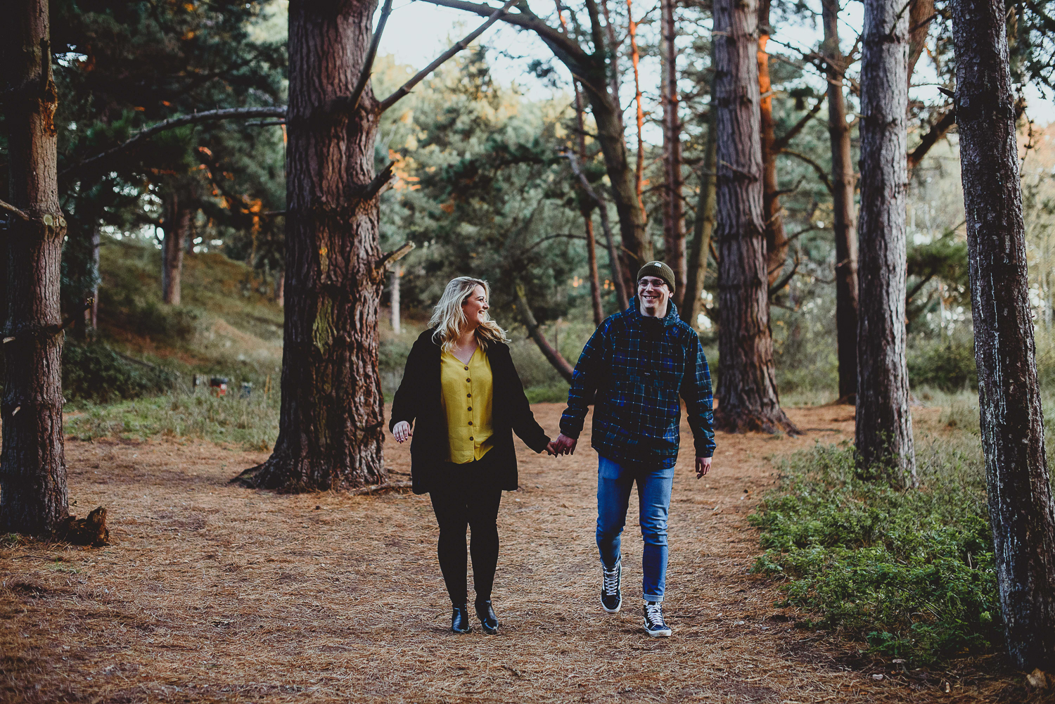 couple walking through woods at wells