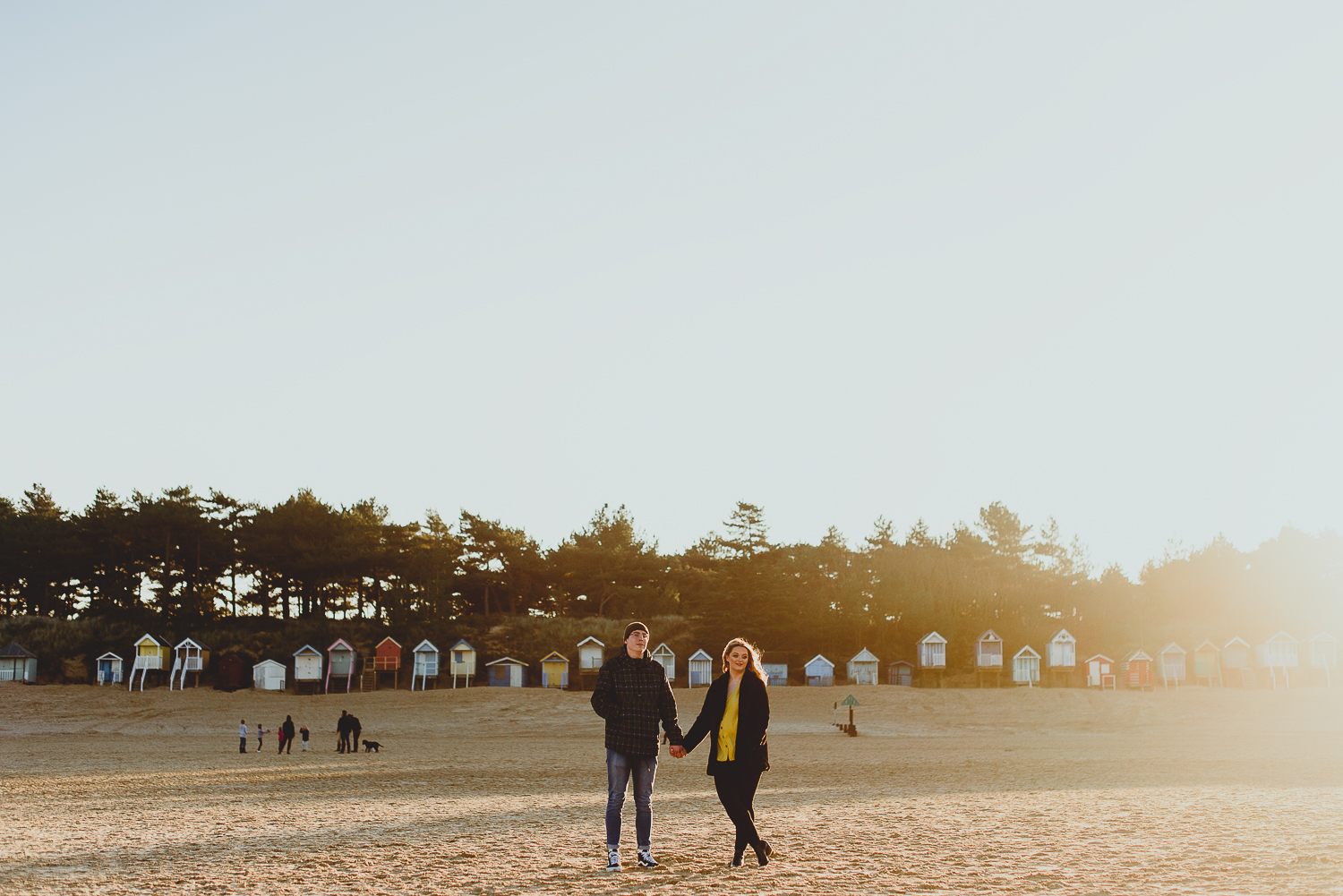 couple standing on beach at wells during sunset