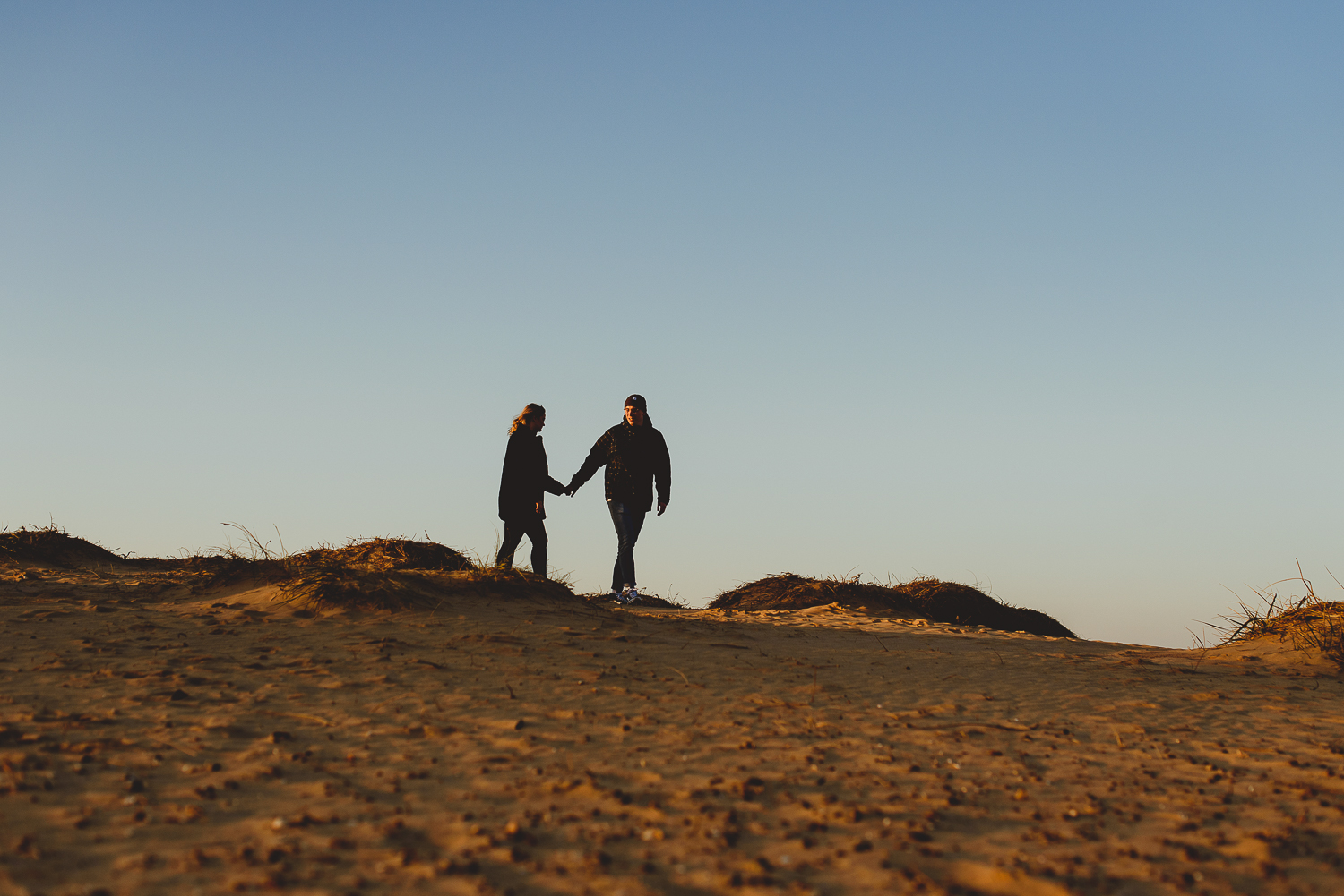 couple walking on sand dunes at wells beach