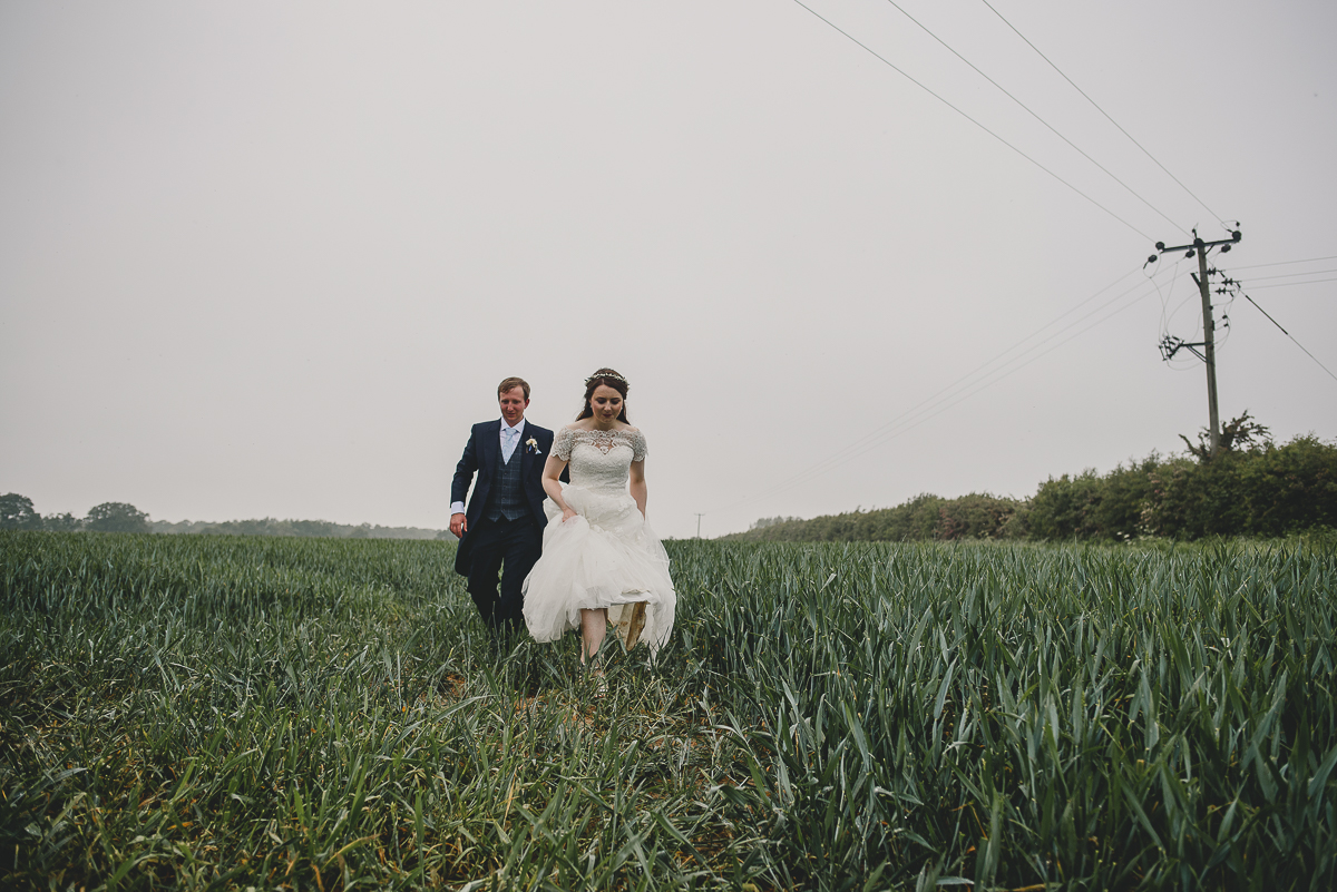 couple walking through field in norfolk farm
