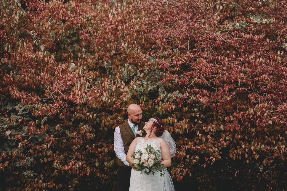 couple in front of bush during autumn