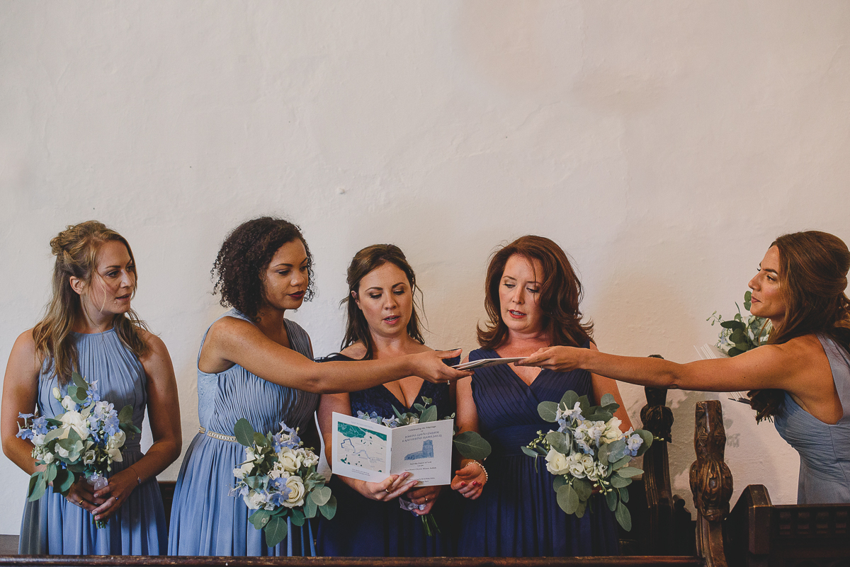 bridesmaids standing in pew at church wedding in beccles