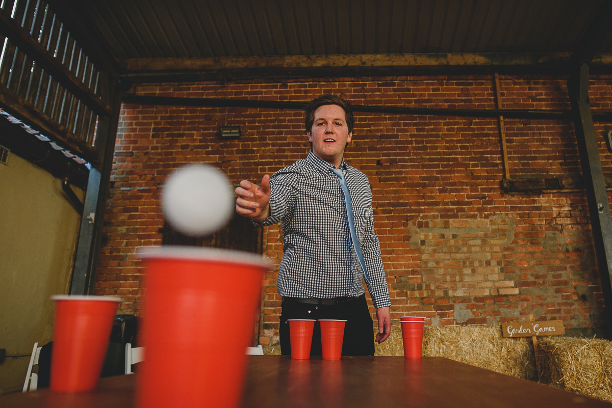 wedding guest playing beer pong