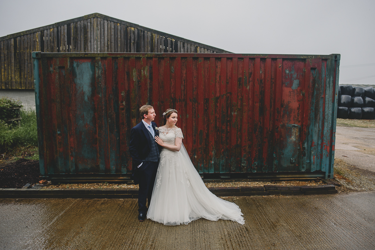 couple standing in rain at farm wedding
