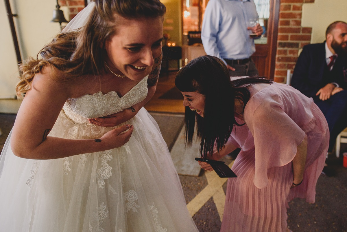 bride and friend bending over laughing