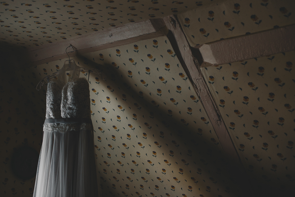 wedding dress hung by window light
