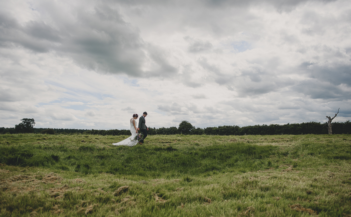 couple walking through godwick barn ruins