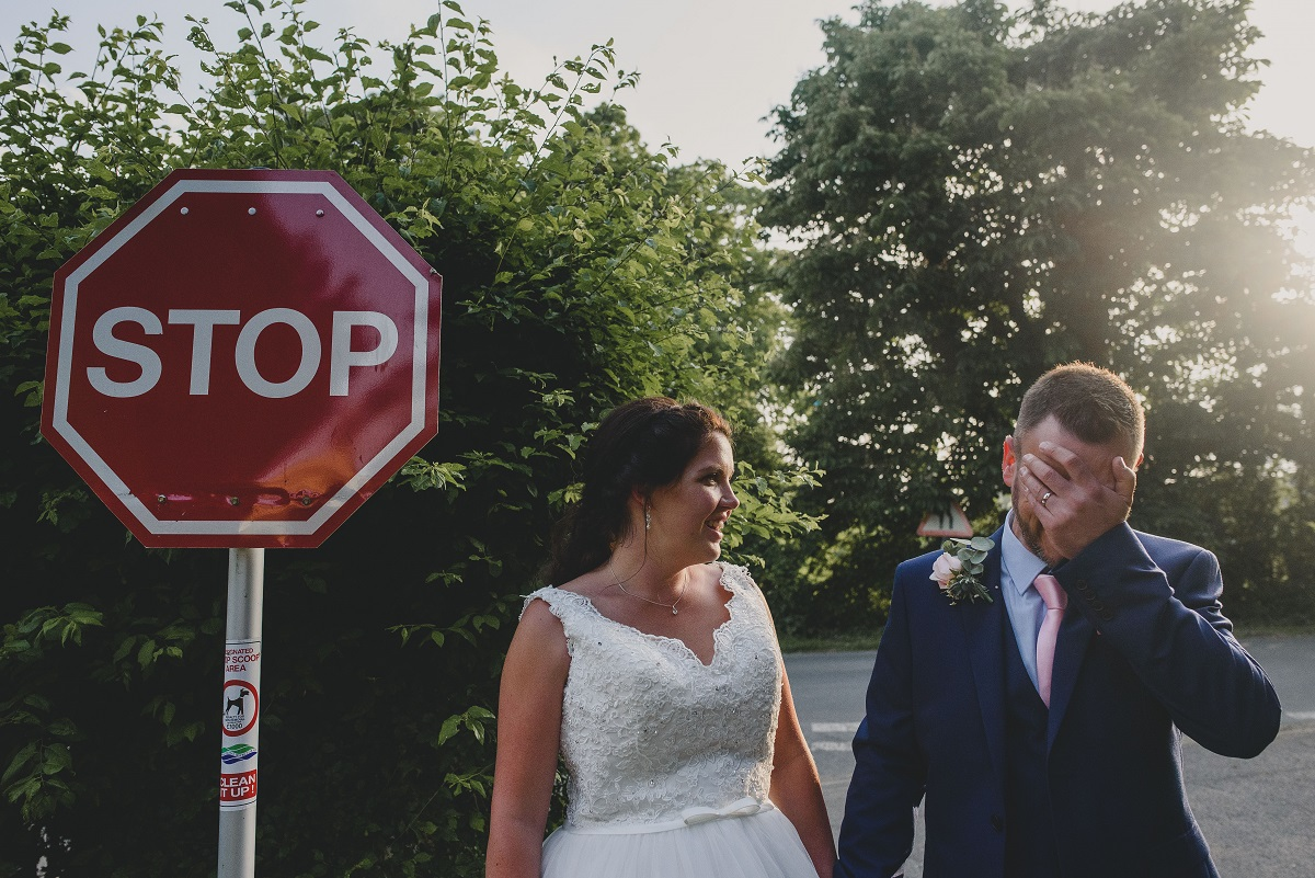 groom and bride standing next to stop sign