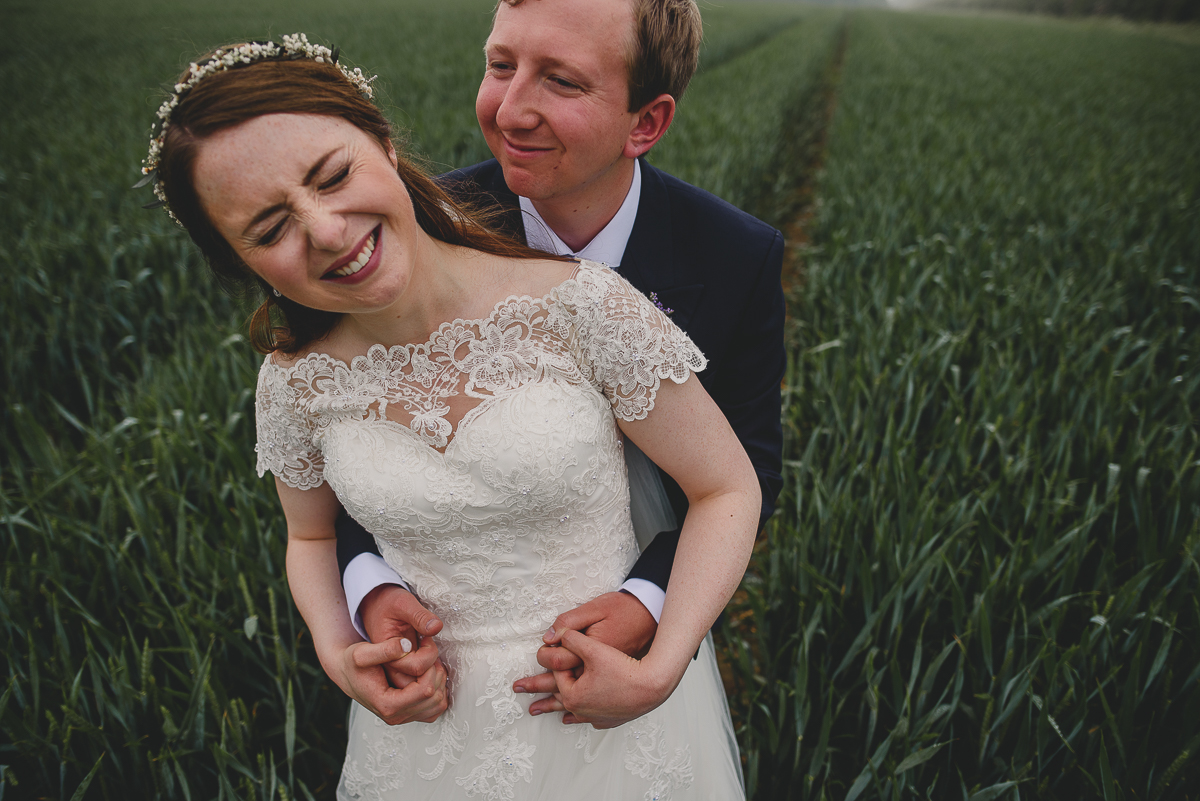 couple smiling and hugging in field