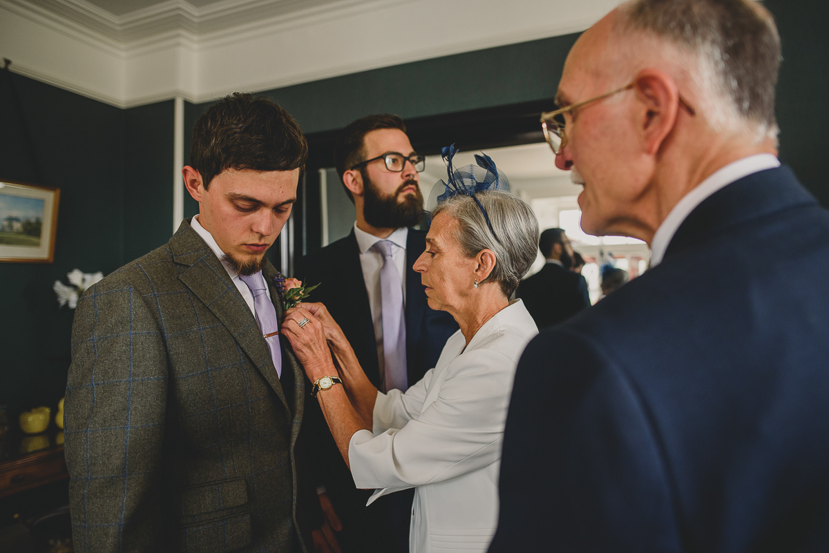 photo of wedding guests helping attach button holes