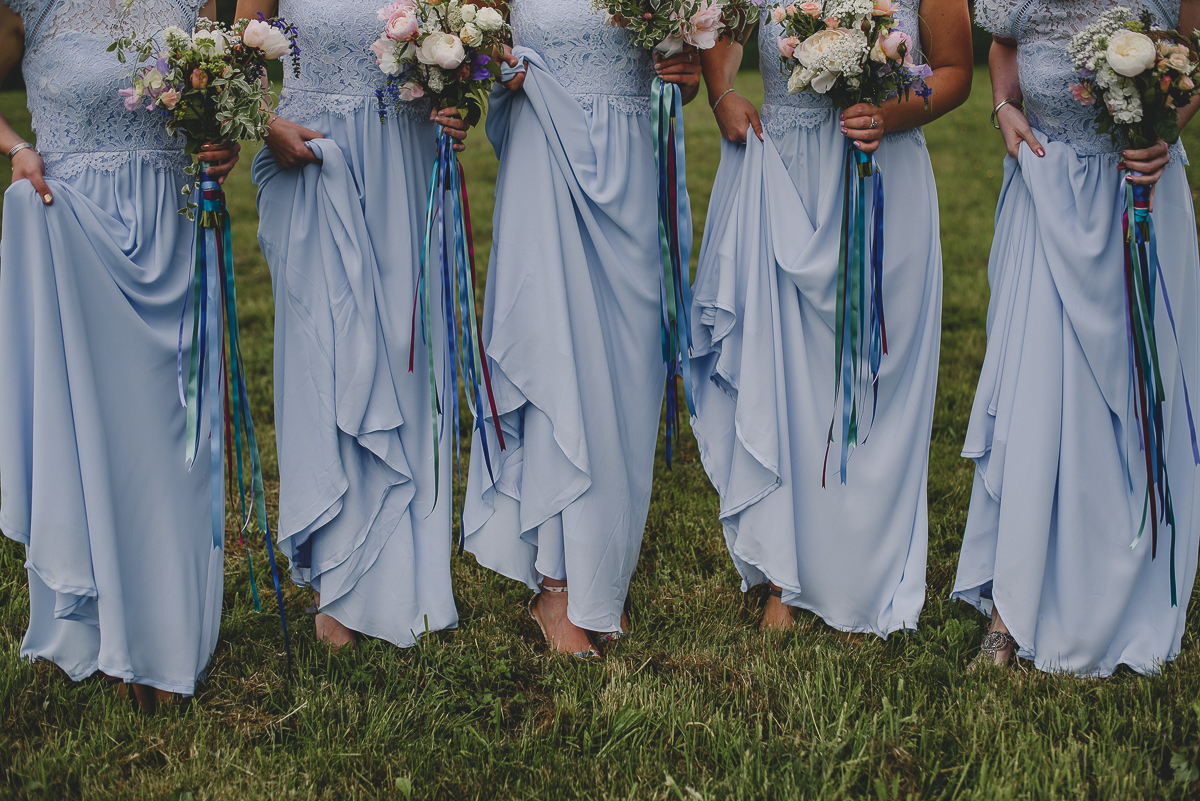 bridesmaids lifting dresses to walk through field