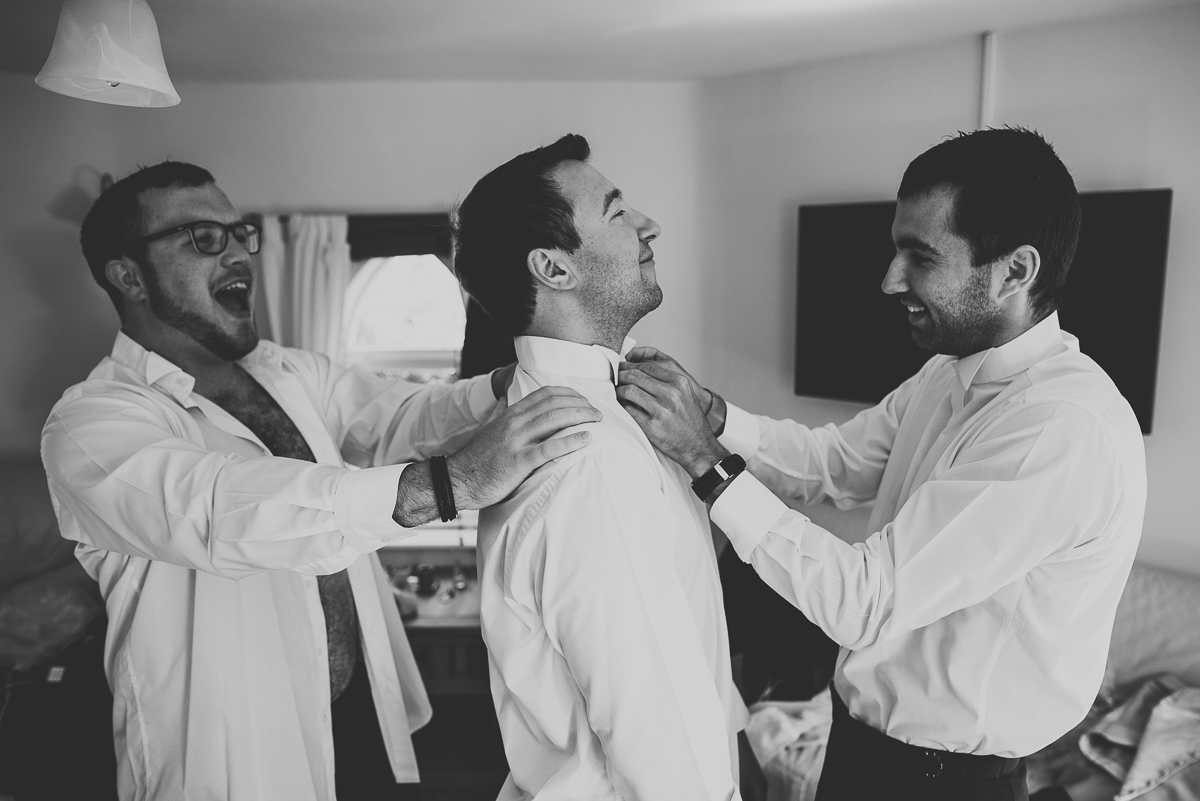 groom having his tie done by best man