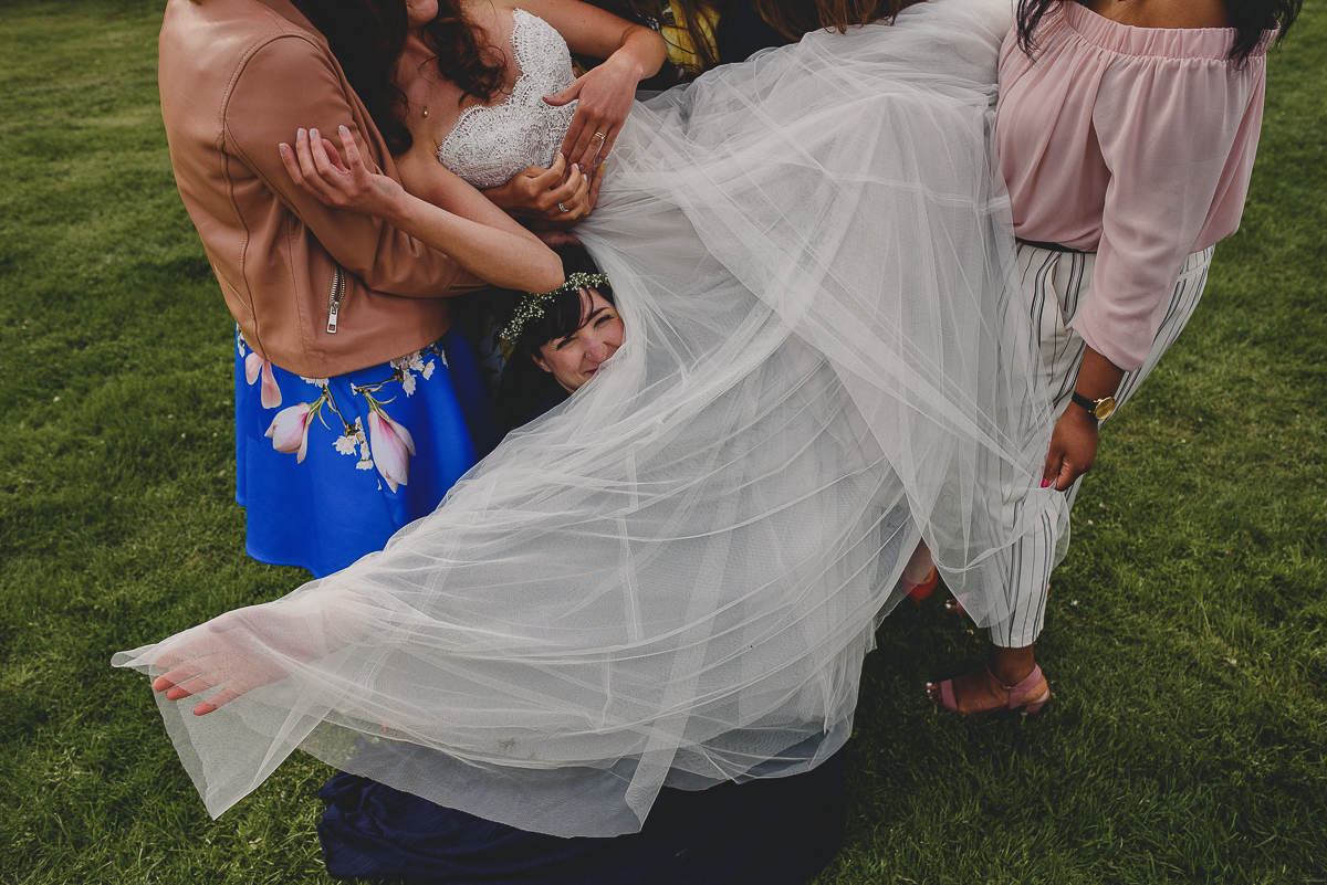 bridesmaid hiding under bride's dress