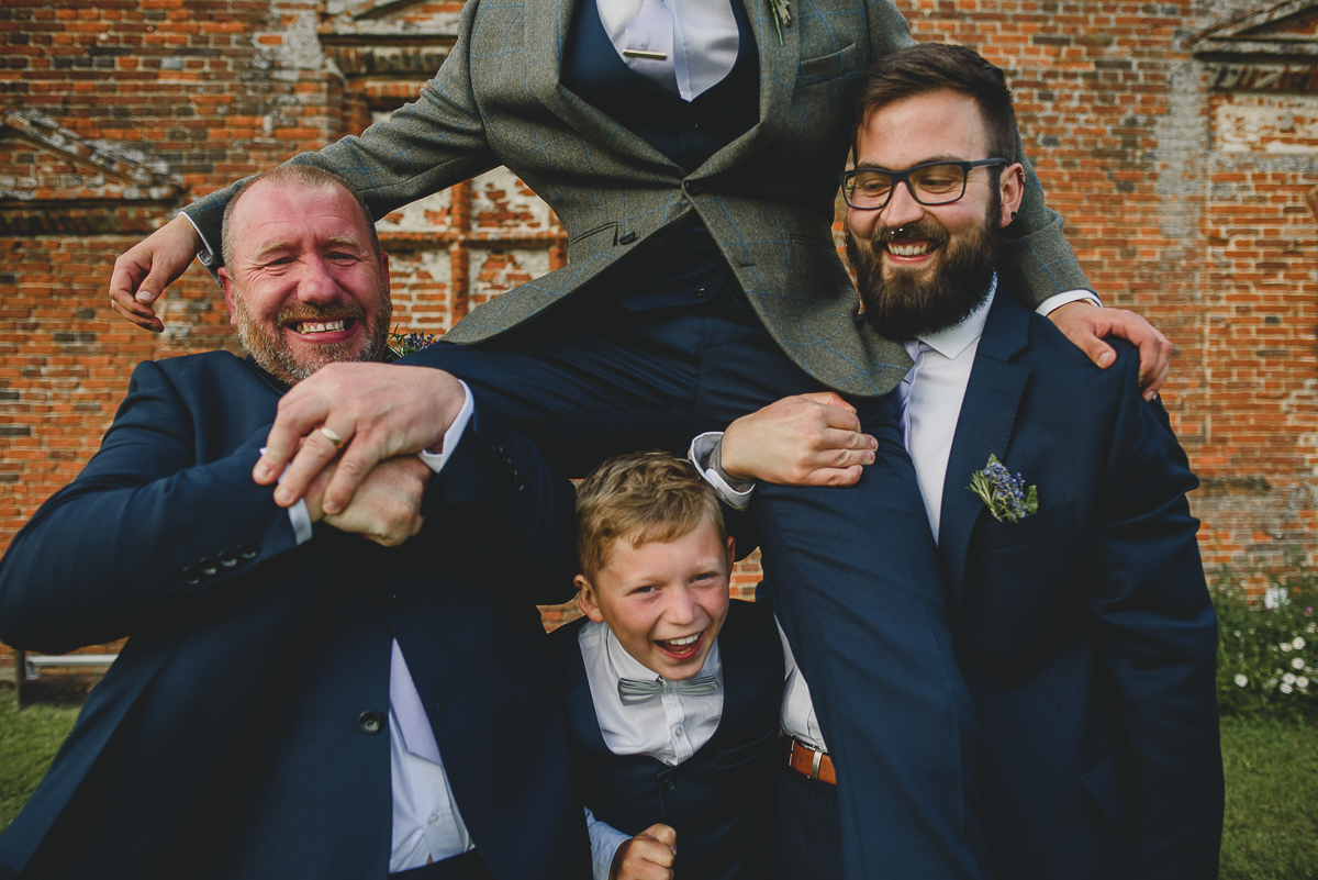 groomsmen lifting groom at godwick barn