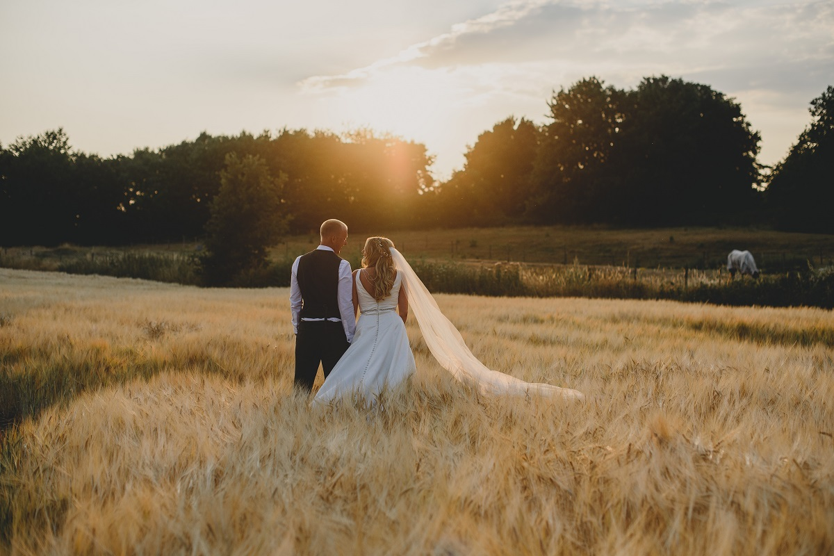 couple standing in field at sunset at spixworth