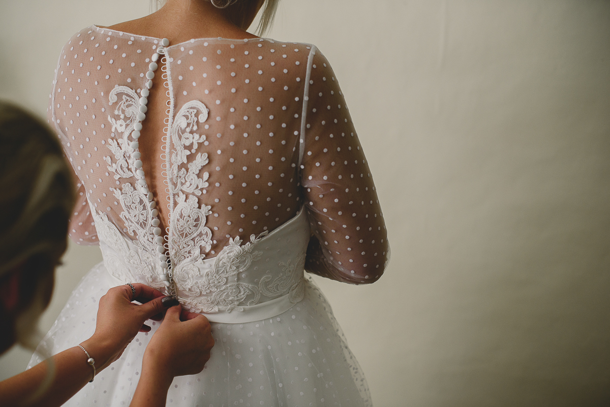 bride having her dress buttoned by bridesmaid