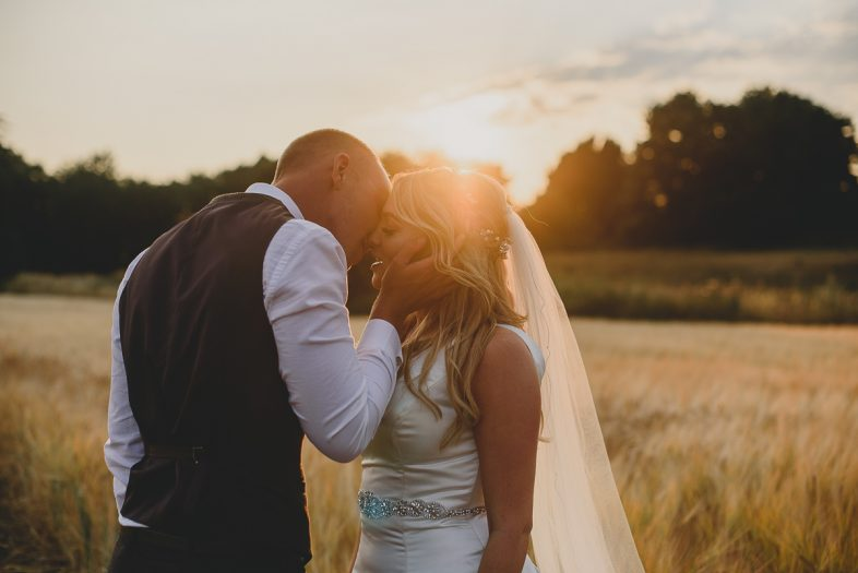 couple kissing during sunset at spixworth hall