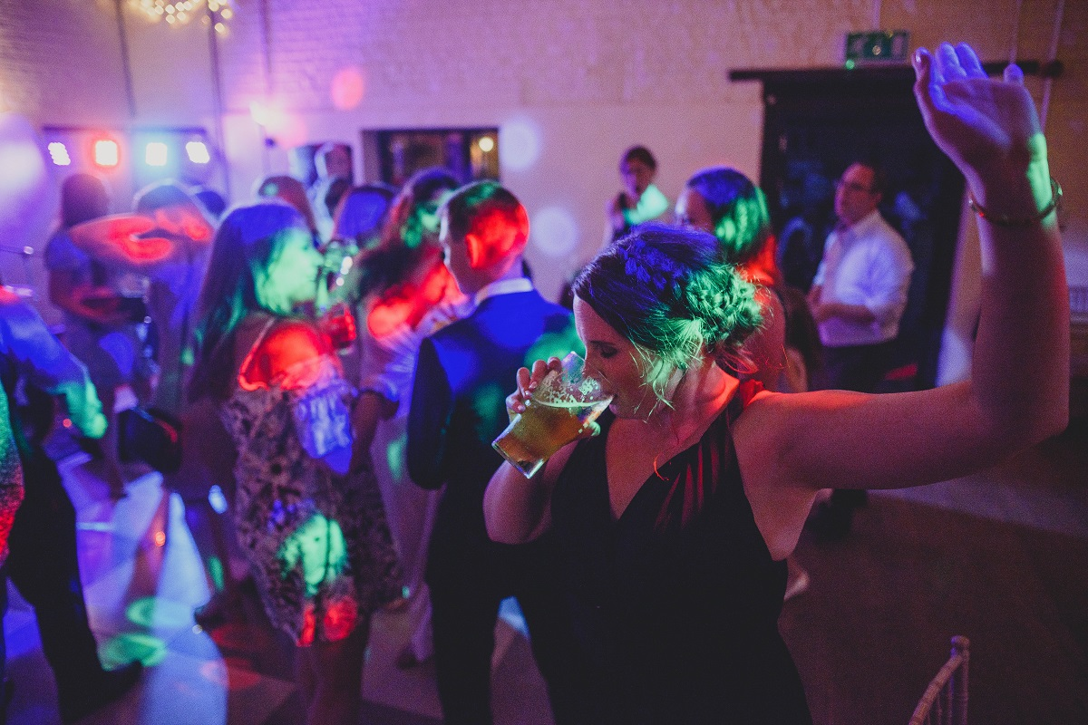 bridesmaid on dancefloor with pint